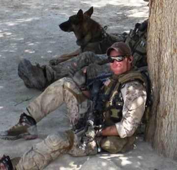 Brad S in military fatigues sitting on ground with comrade and German Shepherd sitting next to him