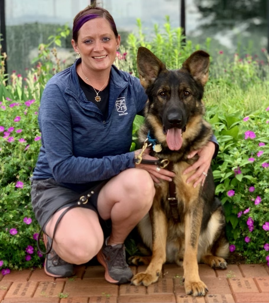"""Trainer Ali in blue Fidelco attire and shorts smiling next to guide dog in training """"Bowie"""" in harness mouth open tongue out"""
