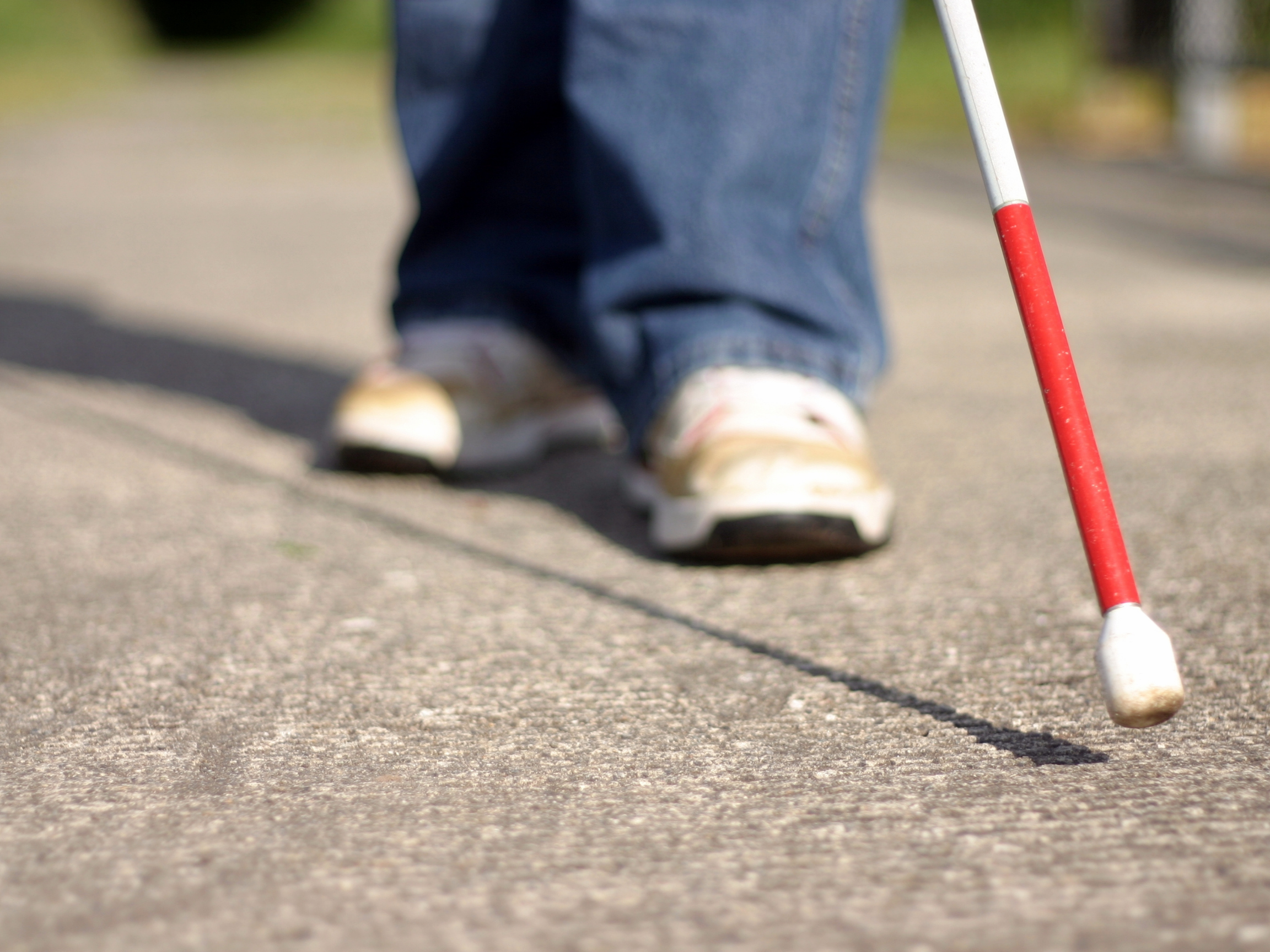 Bottom section of a white cane extended forward the tip above the above the pavement, in the background a faded view of a person's jeans and sneakers.