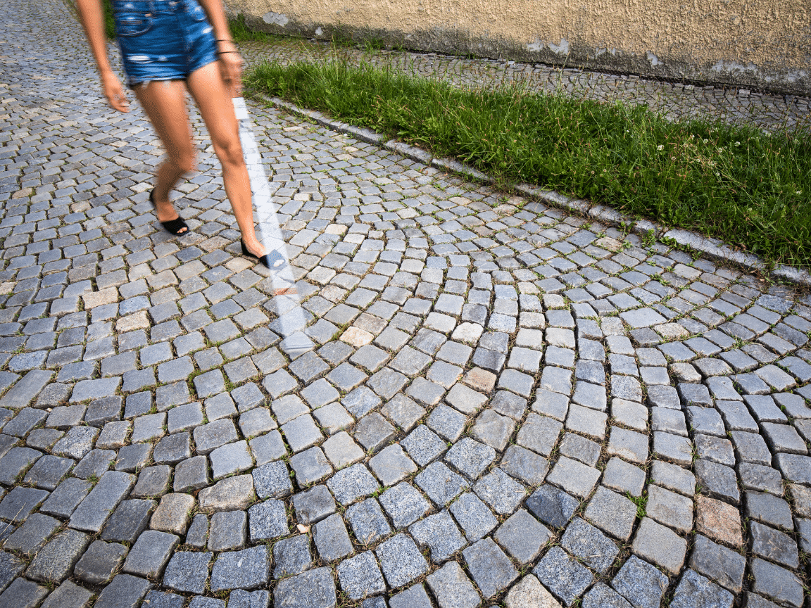 A women in shorts walking down a cobblestone path with a white cane in front of her in motion.